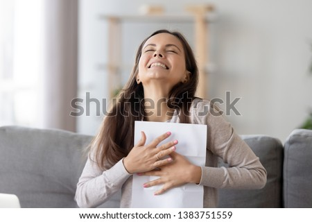 Happy young woman sit on couch excited receive work promotion letter or tax refund from bank, smiling girl student at home feel euphoric get positive feedback or university scholarship. Reward concept