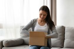Happy young woman sit on couch in living room unpack cardboard box buying goods on Internet, smiling excited millennial girl open carton parcel order, shopping online, good delivery concept