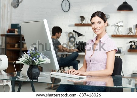 Happy young woman sitting at desk, working with computer, smiling at camera.