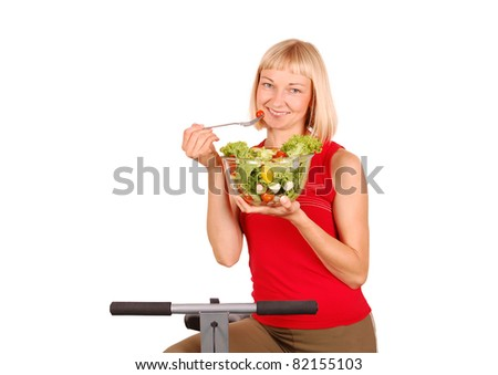 Happy Young Woman Sitting on Bike and Eating Healthy Salad /Healthy Eating For Fitness