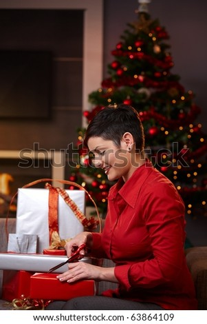 Happy young woman sitting on couch at home, wrapping christmas gifts, using scissors, smiling. ? - stock photo
