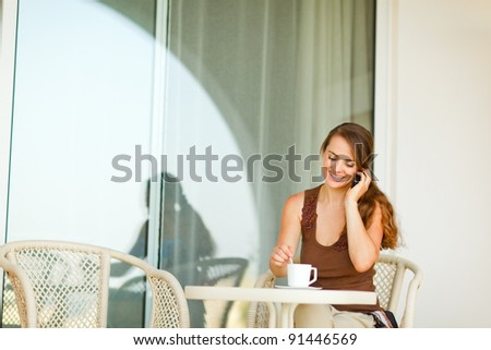 Happy young woman sitting on terrace with cup of coffee and speaking mobile