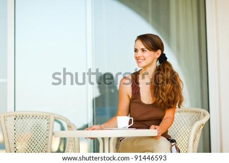 Happy young woman sitting on terrace with cup of tea and looking in corner