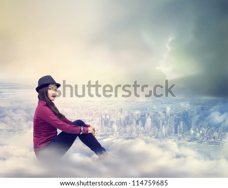 Happy Young Woman Sitting on the Clouds Above the City