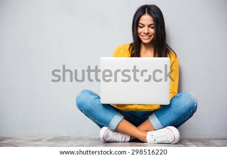 Happy young woman sitting on the floor with crossed legs and using laptop on gray background