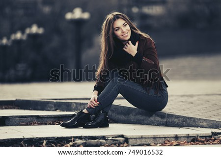 Happy young woman sitting on the sidewalk on city street Stylish fashion model in a fringe leather suede jacket and dark blue jeans