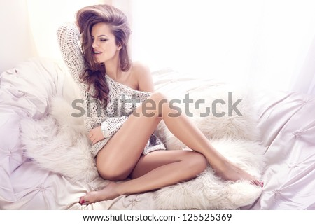 Happy young woman sitting on the white couch with her beautiful legs crossed