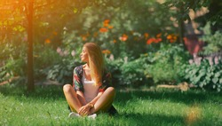 Happy young woman sitting outdoors in yoga position and meditating with closed eyes in summer park Peaceful girl enjoy rest smile and relax in tranquility in spring bloom. Mindset inner peace concept
