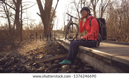 Happy young woman sitting wooden bridge over river, listening music in headphones with smartphone hands and dancing. Positive cyclist listens song in nature. Athlete happy near bike ears earphones.