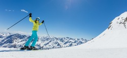 Happy young woman skier enjoying sunny weather in Alps. Winter sport and recreation, lesure outdoor activities.