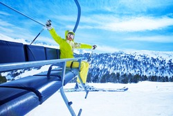 Happy young woman skier on ski lift smiling and cheerfully lifting her hands