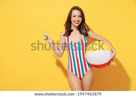 Happy young woman slim body wear striped red blue one-piece swimsuit hold play inflatable beach ball isolated on vivid yellow color wall background studio. Summer hotel pool sea rest sun tan concept
