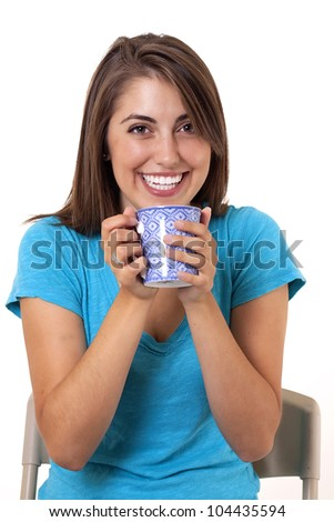 happy young woman smiling as she holds up her coffee mug