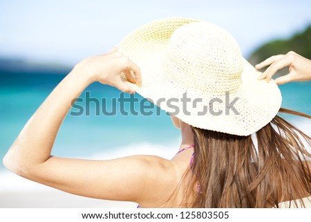 Happy young woman smiling in straw hat with closed eyes on the beach