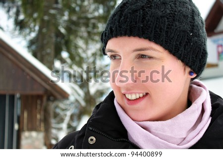 Happy young woman smiling, spending her winter holiday in a mountain cabin