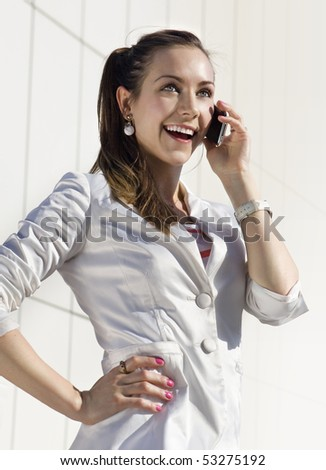 happy young woman speaks by mobile phone on the street