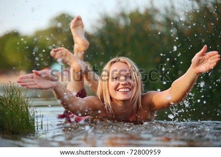 Happy young woman splashing water while swimming