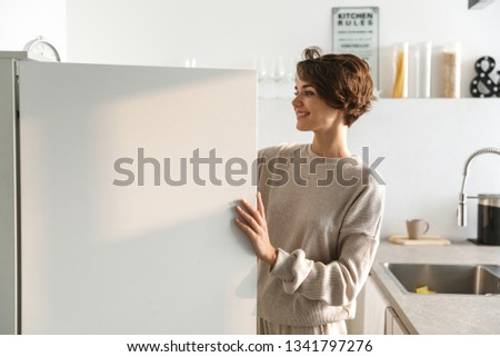 Happy young woman standing at the opened fridge