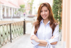 Happy young woman standing crossed arms with smiling face and blurred background