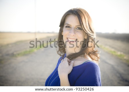 Happy Young Woman Standing Outdoors Smiling to the Camera