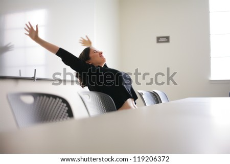 Happy young woman stretching in white office presentation room.