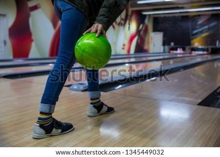 Happy Young woman throwing ball in bowling club- People, leisure, sport and entertainment concept