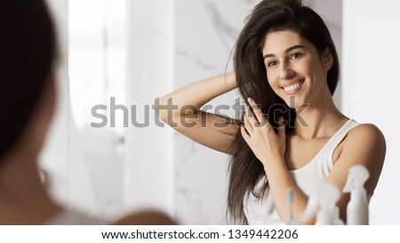 Happy young woman touching her hair and smiling looking in mirror. Home haircare concept