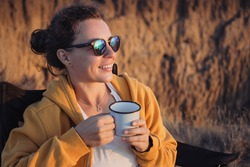 Happy young woman traveler in sunglasses holding iron mug cup with tea or coffee, enjoying ocean sunset scenery in nature landscape, sitting in camp. Travel camping and adventure lifestyle concept.