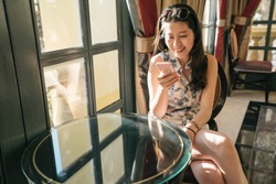 Happy young woman traveler sitting relaxed on sofa at luxury hotel lobby bar in las vegas. cheerful lady tourist typing on cellphone chatting with friend on internet. smiling female texting sms.