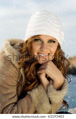 Happy young woman trying to keep warm in the snow