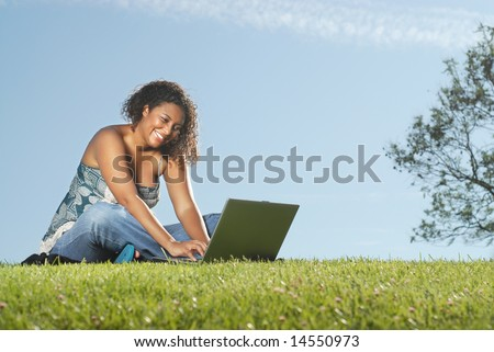 Happy young woman typing away on a laptop while sitting outside