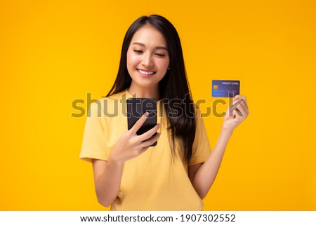 Happy young woman using mobile phone showing plastic credit card standing over yellow background, Online payment, hands holding credit card and using smart phone for online shopping with smile face