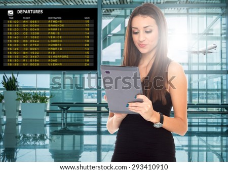 happy young woman using tablet computer at airport terminal