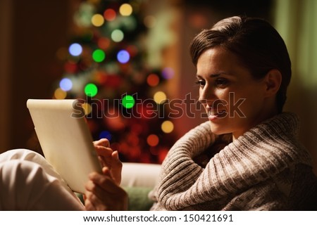 Happy young woman using tablet pc in front of christmas tree