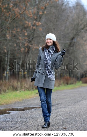 Happy young woman walking along the alley of the park