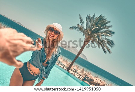 Happy young woman walking on hotel territory near the pool. Summer vacation in Egypt. Stylish fashionable look. Travel, summer holidays and vacation concept - Beautiful woman walking near the pool