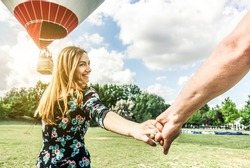 Happy young woman wants to make balloon tour holding boyfriend's hand - Follow me, future together and love concept - Couple of lovers having fun in park outdoor - Focus on hand - Contrast filter