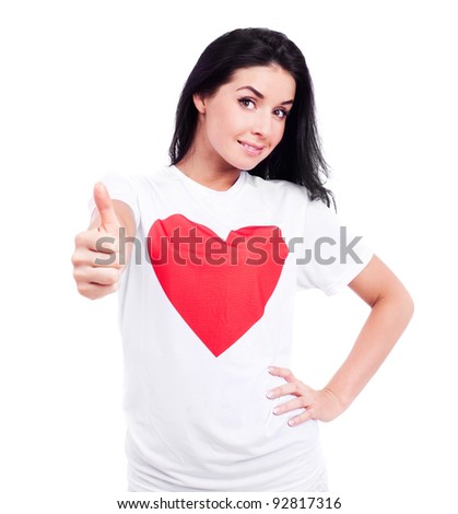 happy young  woman wearing a T-shirt with a big red heart with  thumb up, isolated against white background