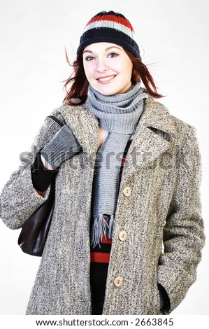 Happy young woman wearing coat and knit hat.
