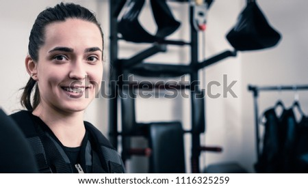 Happy young woman wearing electro muscular stimulation vest #1116325259