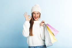 Happy young woman wearing sweater standing isolated over blue background, carrying shopping bags, showing ok gesture
