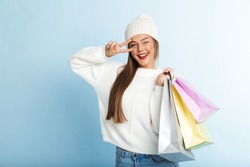 Happy young woman wearing sweater standing isolated over blue background, carrying shopping bags, showing peace gesture