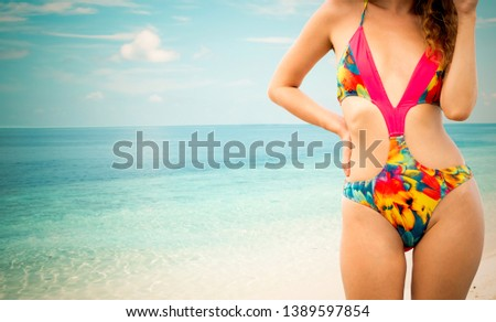 Happy young woman wearing swimsuit at tropical sand beach resort in summer for holiday travel vacation. #1389597854