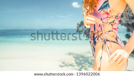 Happy young woman wearing swimsuit at tropical sand beach resort in summer for holiday travel vacation. #1396022006