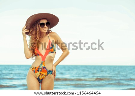 Happy young woman wearing swimsuit having good time at tropical beach in summer for holiday travel vacation. #1156464454
