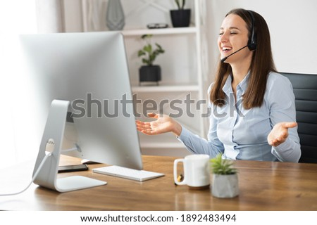 Happy young woman with a headset talking online via video connection on the trendy PC. A businesswoman with handsfree garniture waving into webcam with a pleasure smile Stok fotoğraf ©