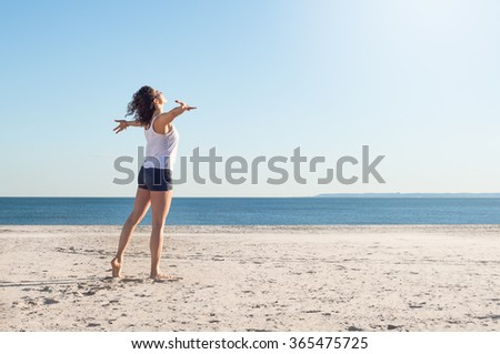 Happy young woman with arms outstretched at beach on a bright morning. Beautiful young woman with arms stretched out standing on a beach. Happy young woman feelling good and relaxing at the beach.
