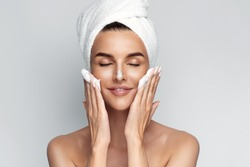 Happy young woman with bath towel on her head takes care of her skin face, applies cleansing foam after shower, smiling and closed eyes, isolated on grey background. Face wash.