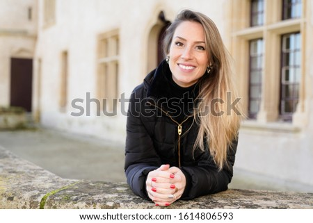 Happy young woman with blonde long hair tourist posing around ancient streets