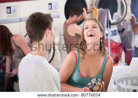 Happy young woman with boyfriend laughs out loud in the laundromat